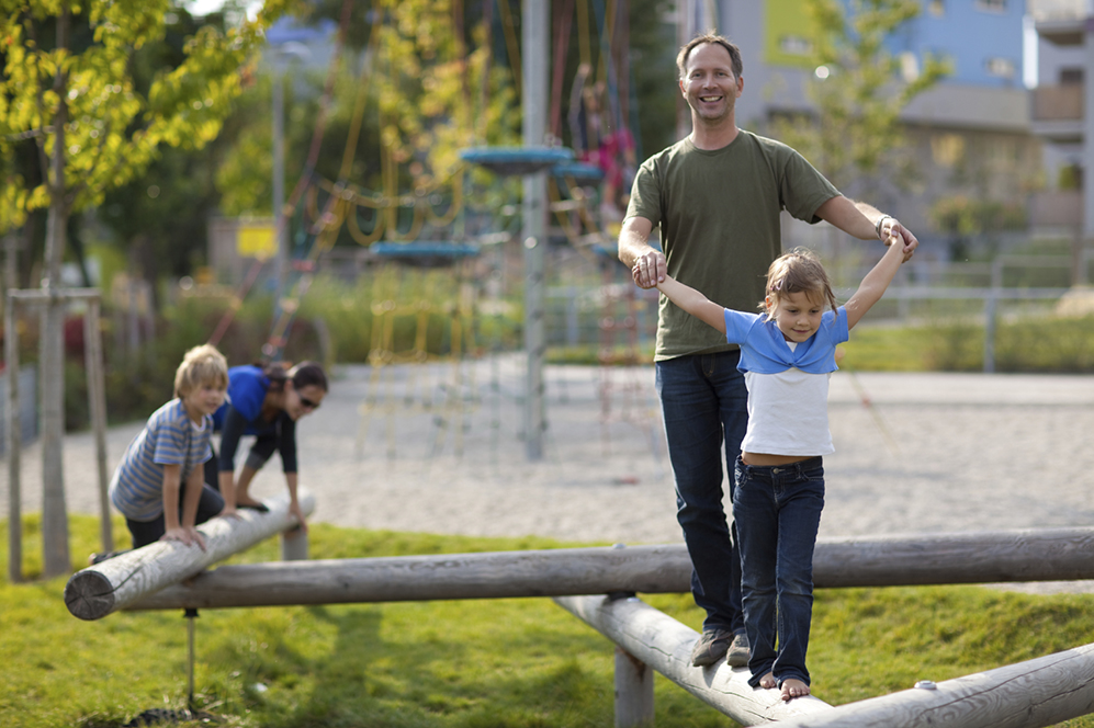 family  on wooden bar at playground